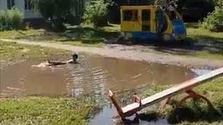 Мальчик плавает в луже